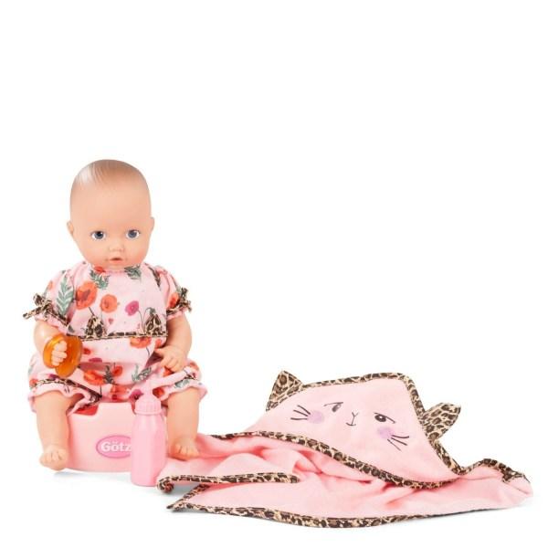 Poupée Aquini Bébé fille avec un pyjama rose à fleur avec des imprimés léopard à la ceinture et sur les bras. Le bébé est sur un pot rose, elle a une tétine dans ses mains, il y a un biberon rose et une cape de bain rose avec des liserés léopard