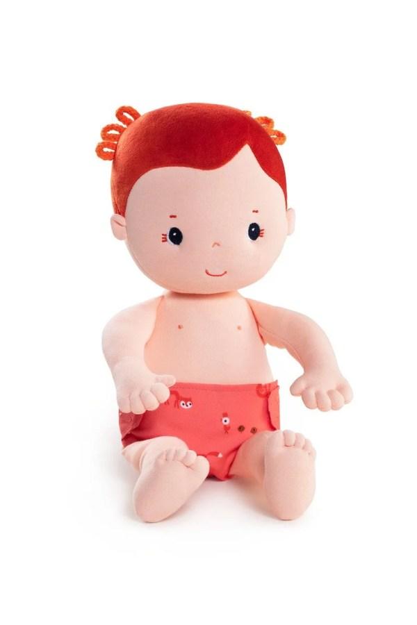 La poupée en tissu Rose de 36 cm tient assise.