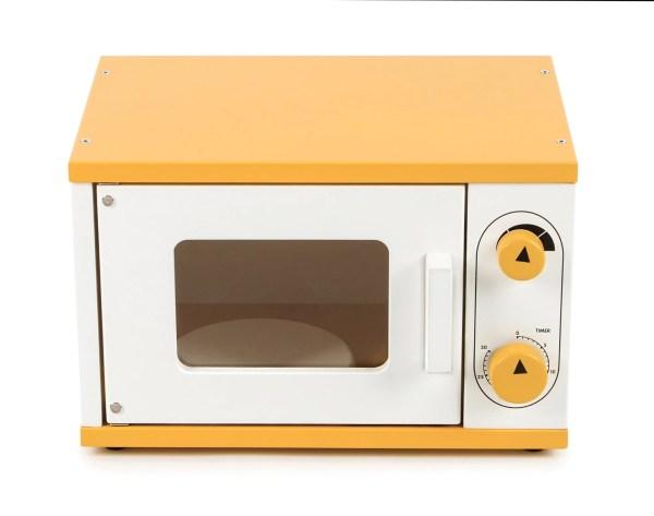 """Equipé d'un plateau tournant et de boutons qui """"cliquent"""" comme les vrais appareils, ce four à micro-ondes en bois est un jouet qui est de couleur orange et blanche et qui est tout ce que dont on peut rêver pour se créer de belles histoires."""