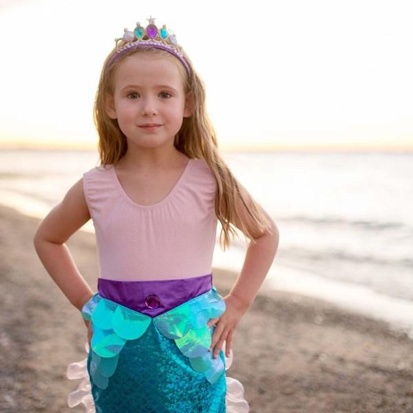 Jupe de sirène portée par une enfant en gros plan sur une plage