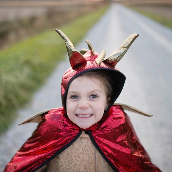 Cape de Dragon rouge et or portée par une enfant qui fait une grimace en gros plan
