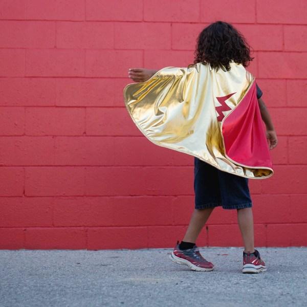 Cape réversible super héros portée par un enfant de dos côté or