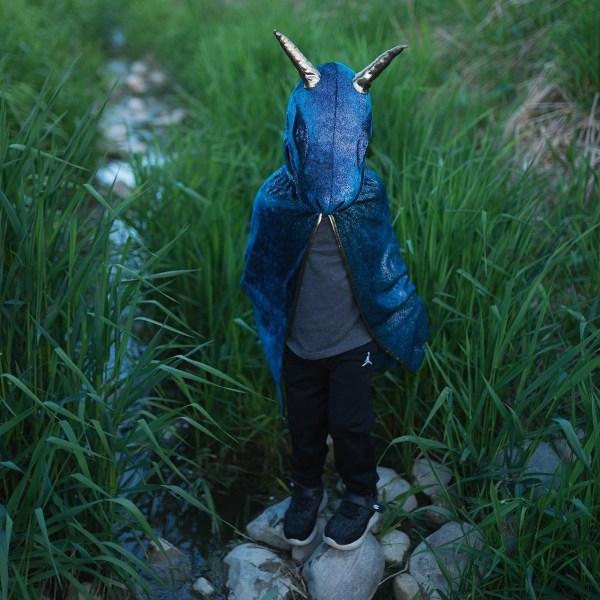 Cape de dragon bleu portée par un enfant sur des cailloux