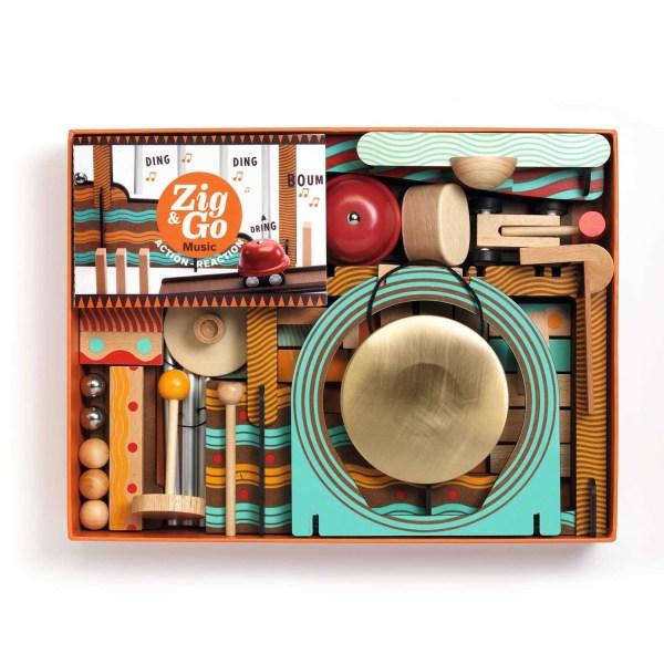 intérieur de la boite du jeu Zig & Go Music avec une clochette des dominos des billes en métal et en bois des rampes un gong et d'autres accessoires