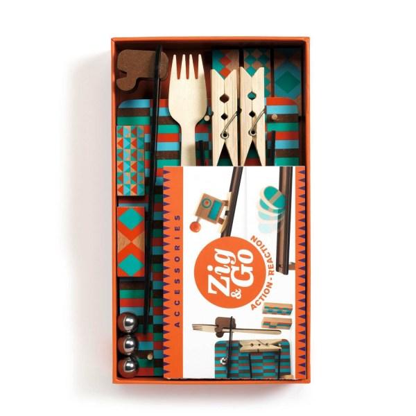 intérieur de la boite du jeu Zig & Go Fork avec 2 pinces à linge 1 fourchette 3 billes des dominos et un petit panneau avec des rampes
