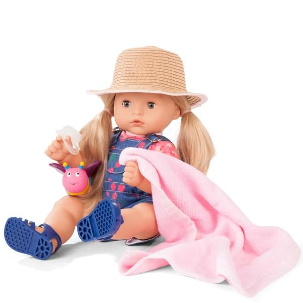 Poupée Maxi Aquini Fille Blonde avec un chapeau de paille des sandales bleues, une salopette en jeans avec des cerises, une serviette rose, une tétine et un jouet de bain