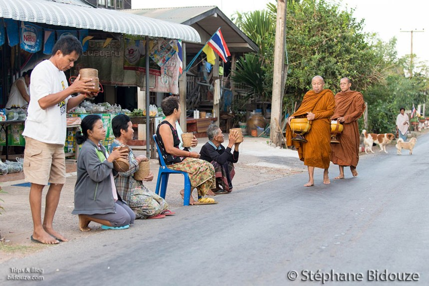 People giving monk's daily alms in Thailand