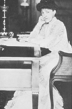 Photo of Edith Wharton sitting at a desk.