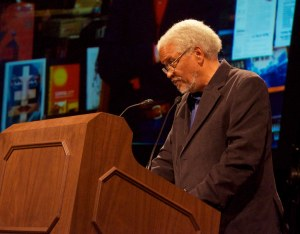 Photo of Ishmael Reed standing at a podium.