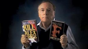 Photo of James Patterson holding up two of his books.