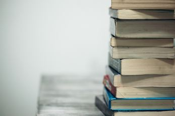 Photo of a stack of books on a table.