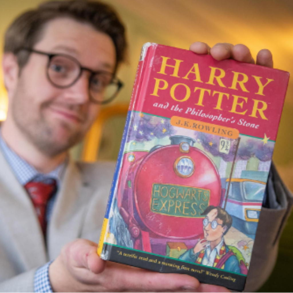 A man holds a first edition Harry Potter book.