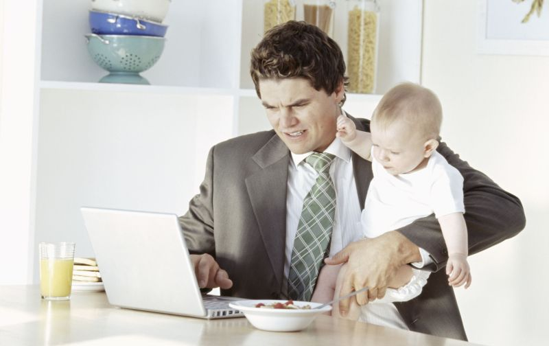 Business man holding son (18-24months), using laptop at table