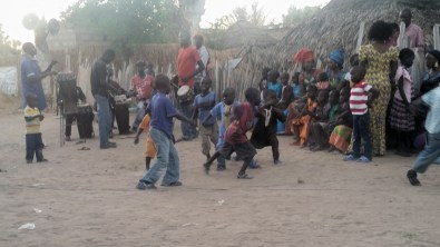 Kids dancing at a Baptism as night falls