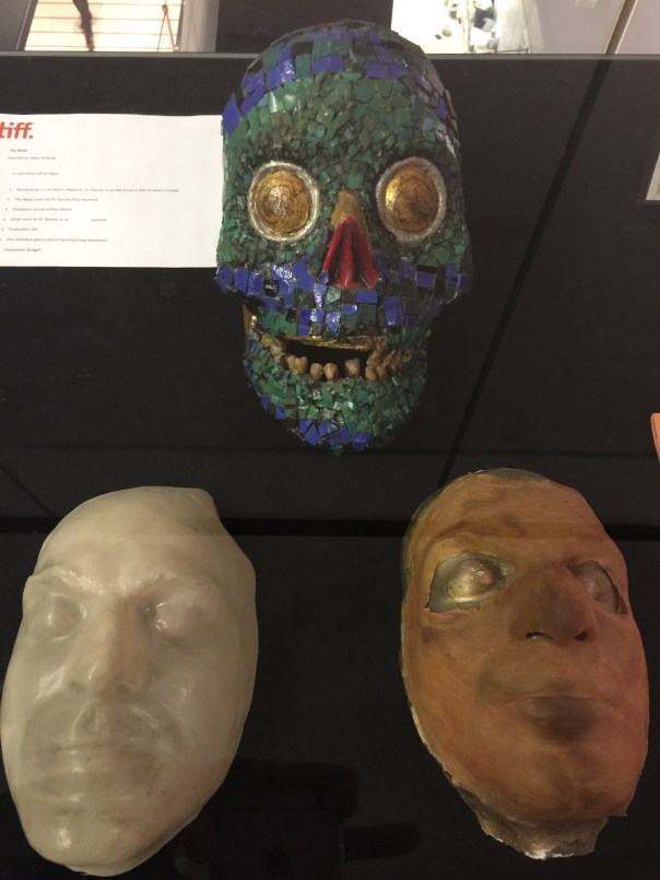The original masks, safely encased in glass outside the theatre.
