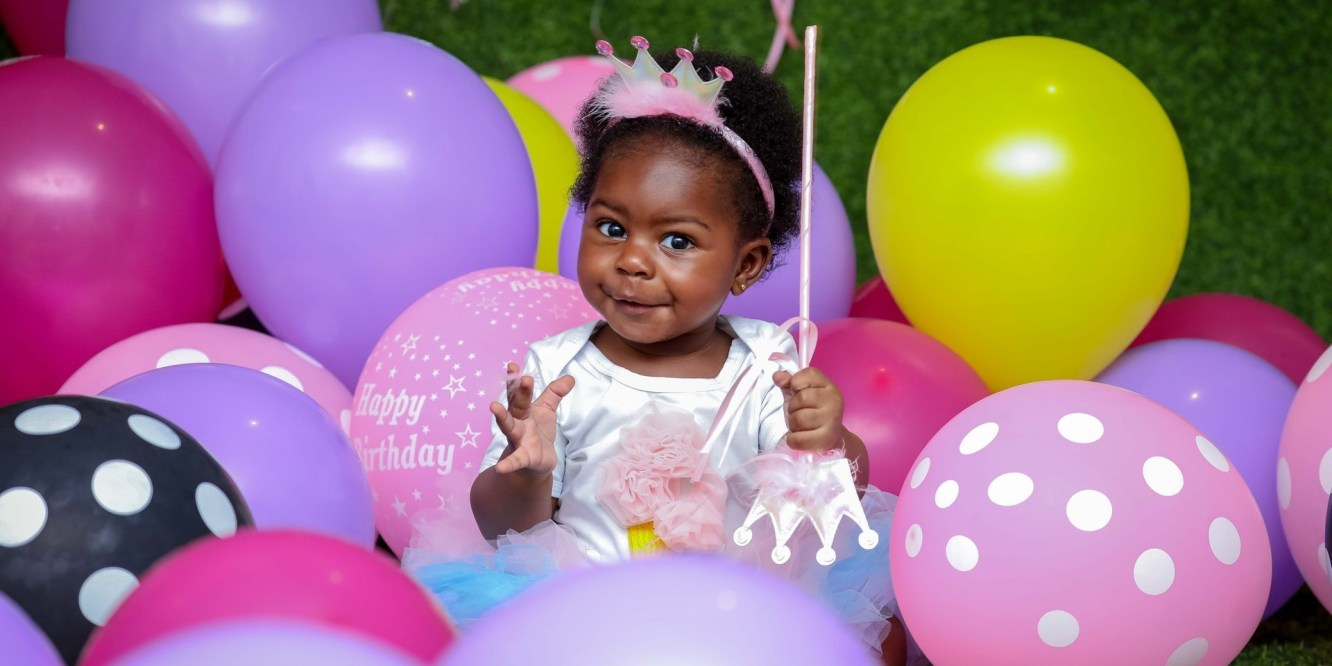 African baby surrounded by birthday balloons
