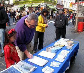 帶著女兒在反迫害徵簽表上簽字的英國先生