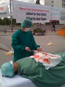 在國際器官移植會議開會地點前,法輪功學員模擬演示中共活摘器官。