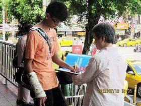 一位青年右手受傷包紮,仍以左手簽下名字。