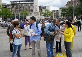 達姆廣場上,路人專注聽法輪功學員講真相
