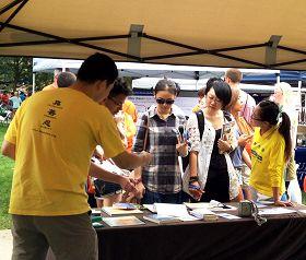 前來參加活動的學生紛紛駐足大法展位,了解法輪功真相。