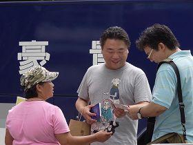 '李香蘭(左一著粉色衣服者)發《九評共產黨》及法輪大法簡介給大陸觀光客'