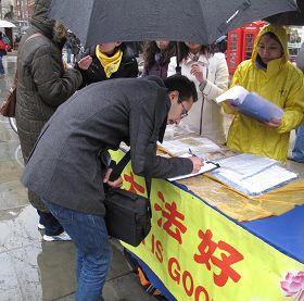 '在倫敦聖馬丁廣場,英國民眾在雨中仍踴躍地在給國會議員的請願信上簽名'