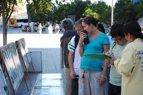 民眾觀看法輪功真相展板並簽名支持反迫害