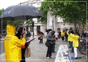 圖1、2:二零一三年六月十五日倫敦聖馬丁廣場:英國法輪功學員在雨中堅持進行講真相,徵簽反迫害活動。