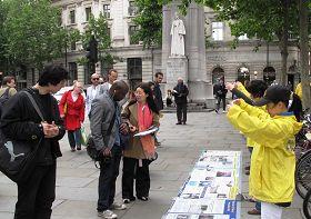 圖6:大雨過後,法輪功學員寧靜祥和的煉功場面立即吸引很多路人駐足觀看。