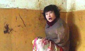 柳志梅常常不穿褲子,只裹一條單薄的床單坐在炕上。身後牆上的黑色黃色是她塗抹大便留下的印跡。(攝於二零一一年冬)