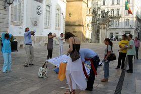 Coimbra的民眾看真相展板和演示功法,簽名支持反迫害