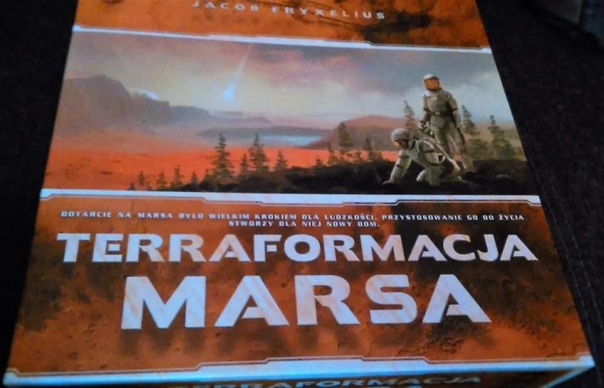 Wieczko pudełka do gry, z grającą pierwsze skrzypce grafiką przedstawiającą astronautów na Marsie.