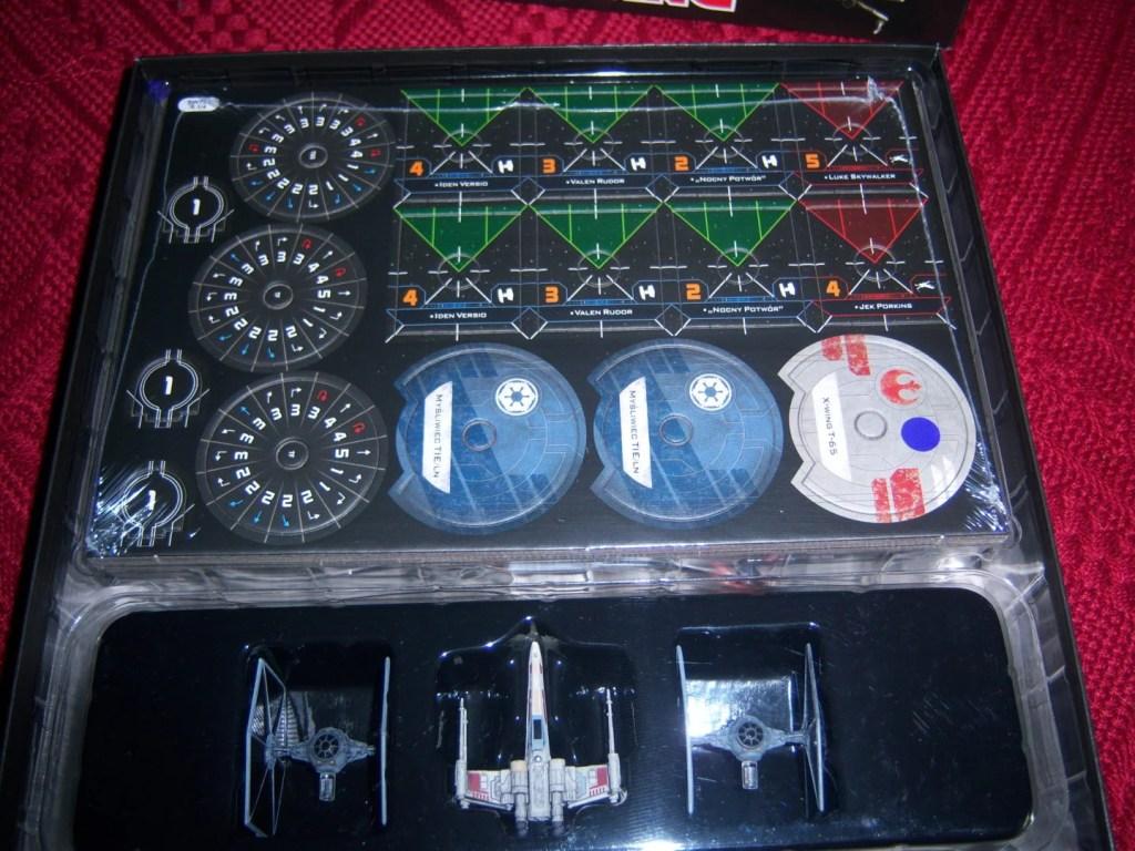 Wnętrze pudełka po sciągnięciu wieczka. Widzimy wypraskę z elementami gry i trzy myśliwce.