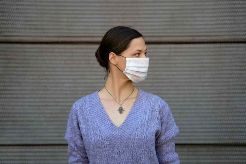Covid-19 women in blue sweater wears white face mask