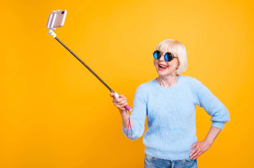Woman in blue sweater holds out selfie stick