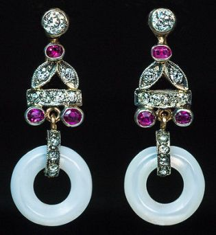 Aretes Art Decó de oro con diamantes incrustados y rubíes. Estan unidos a dos discos de madre perla.