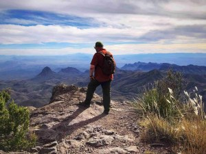 adam brower peering off cliff Views from the South Rim Trail in Big Bend National Park