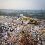 yellow excavator on piles of trash