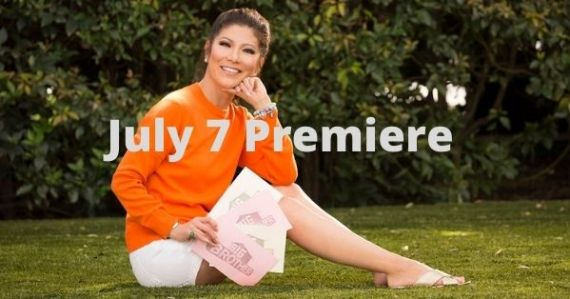 Julie Chen holding Big Brother cards sitting on the grass