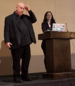 Lynn Bender next to a podium, Gwen Shapira smiling behind it with laptop open