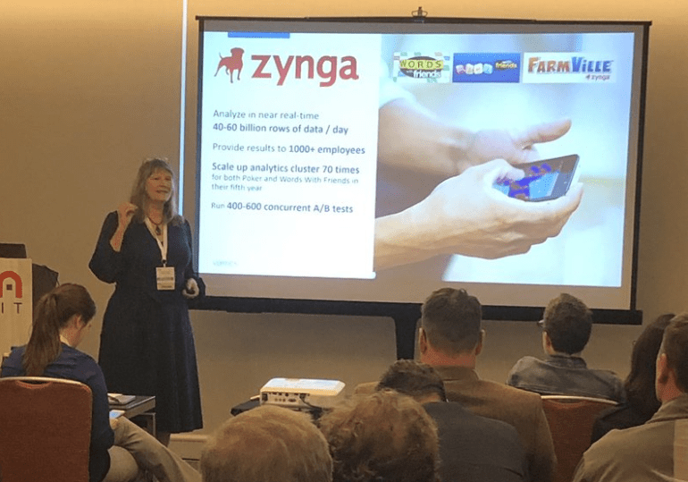 Paige Roberts presenting to full room with Zynga case study slide showing