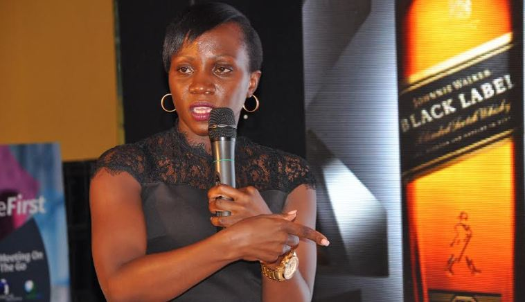 "UBL Head of Spirits Annette Nakiyaga addressing guests during the launch of the ""Paint The World Black"" promotion"