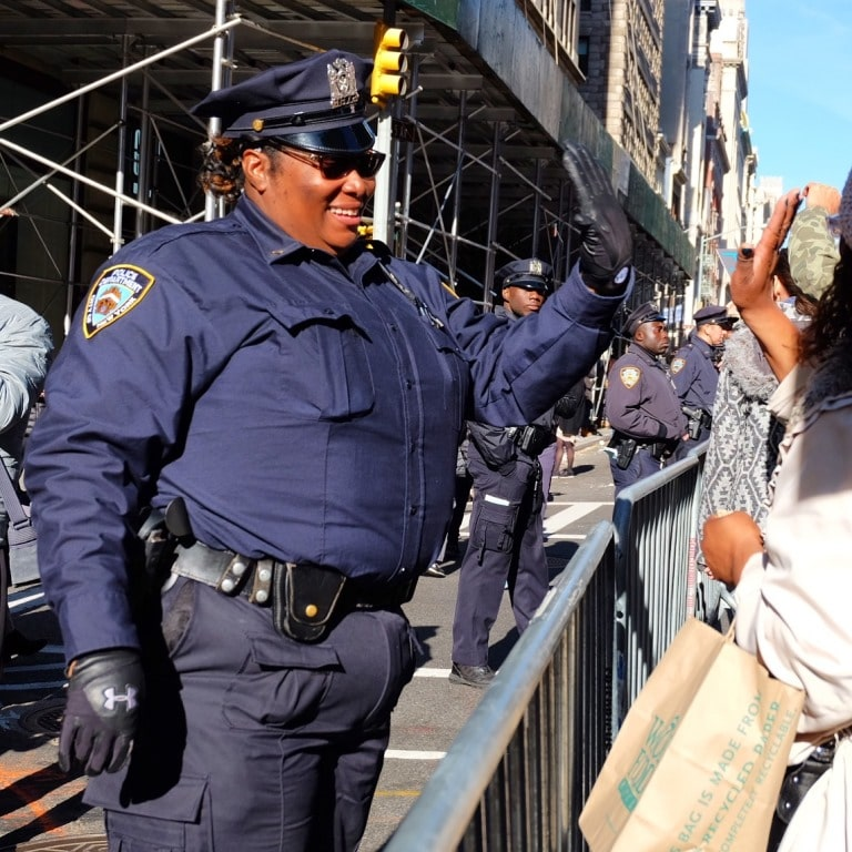 An NYPD cop high-fiving the crowd