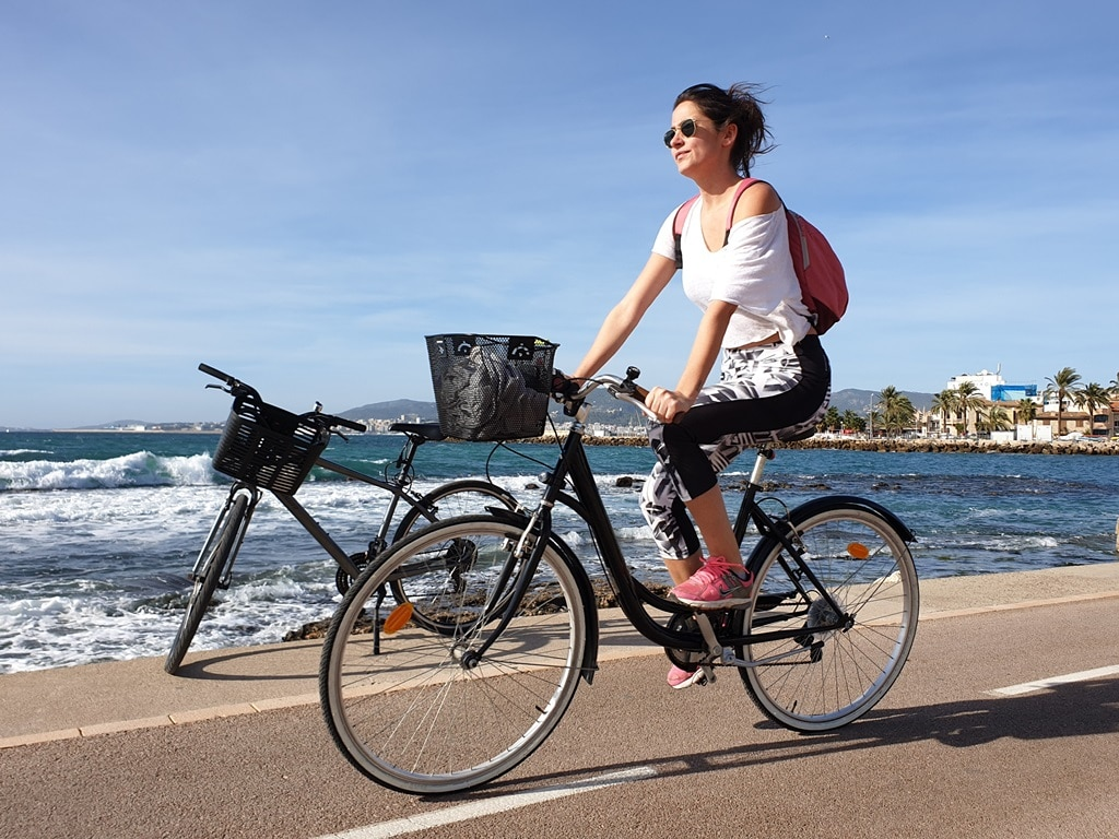 The bike route, sea and passing cyclist at El Molinar