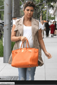 Kourt K. being ultra casual pairing the trench vest with distressed boyfriend jeans and a white tee.