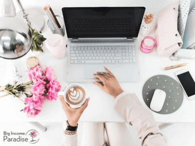 pink peonies, silver laptop, white table, coffee in a white mug, phone, white mouse, mouse pad with dots, pink bag and silver lamp