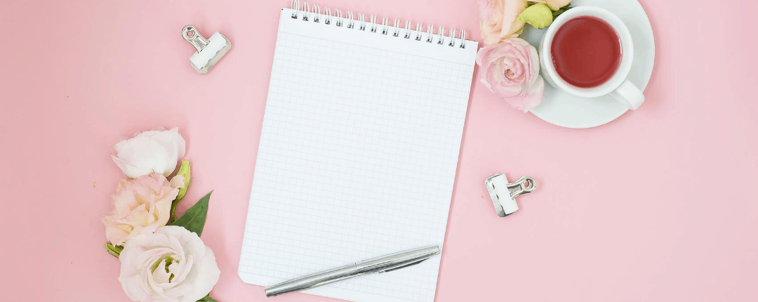 Feminine home office workspace. Notebook with copyspace. Flat lay, magazines, social media, top view. Pink flowers and tea on pastel pink background. Wedding to do list. Mockup planner.