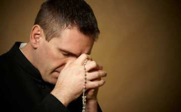 Priest Praying with Rosary
