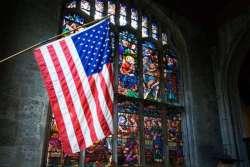 u-s-flag-and-stained-glass-window-inside-catholic-church